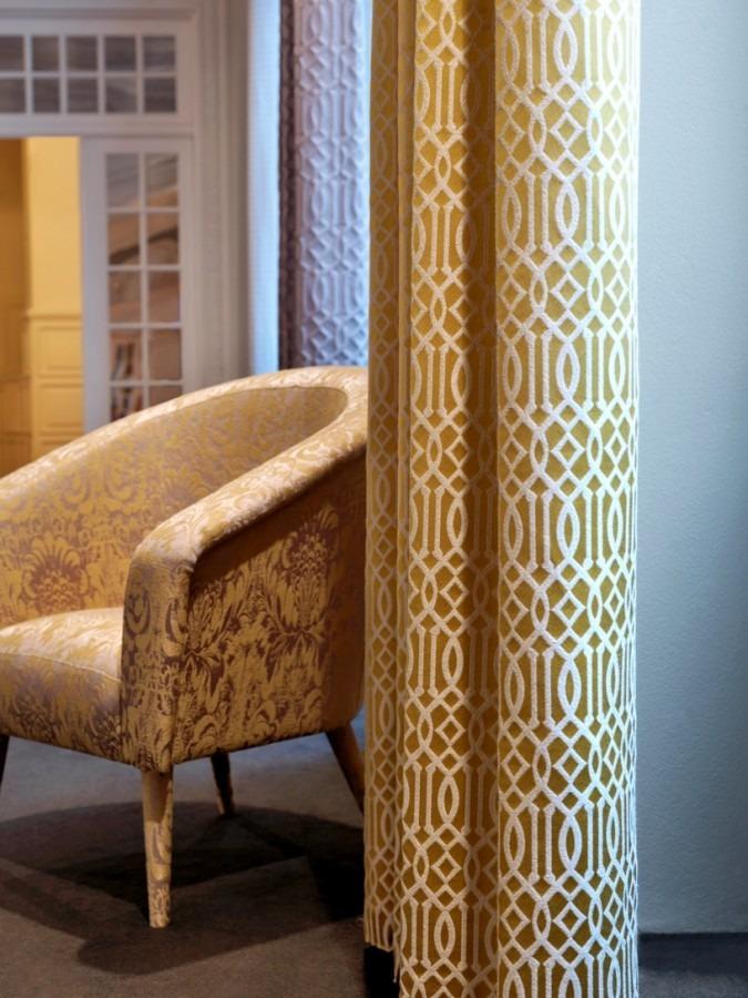 Luxusní bytový textil ve zlaté barvě s propracovaným světlým vzorem