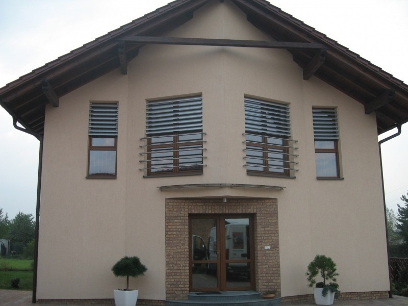 Horizontální slunolamy na oknech domu s žlutou omítkou