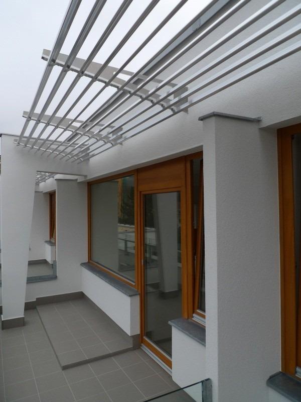 Horizontální slunolam nad balkonem se skleněnými dveřmi