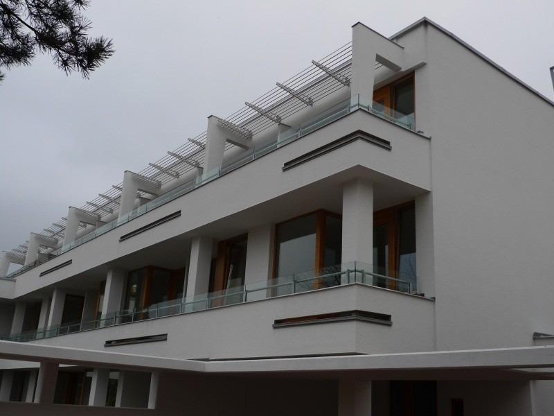 Horizontální slunolam nad balkony bílého domu