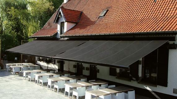 Černá roztažená markýza nad stoly a židlemi