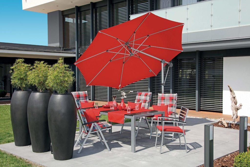 Červený slunečník roztažený nad stolem s židlemi
