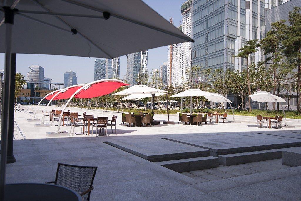 Slunečníky bílé a červené roztažené nad stoly