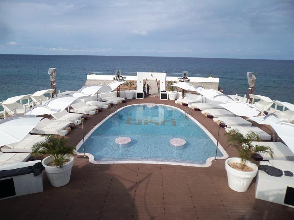 Slunečníky bílé roztažené u bazénu