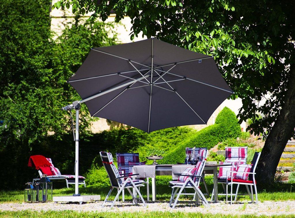 Černý roztažený slunečník nad zahradními židlemi