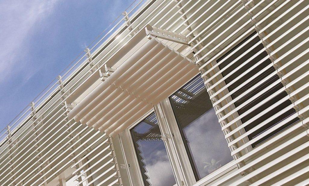 Bílý slunolam na domě kolem okna