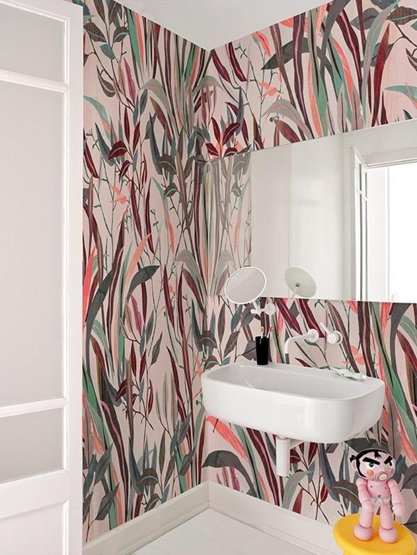 Barevná tapeta v koupelně s umyvadlem, dvěma zrcadly a růžovou figurkou