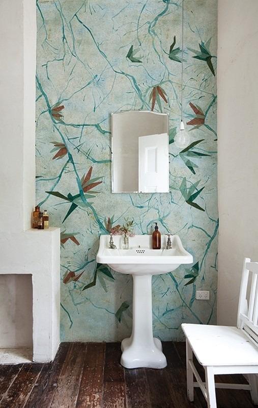 Koupelna s modrou květinovou tapetou, umyvadlem a židlí