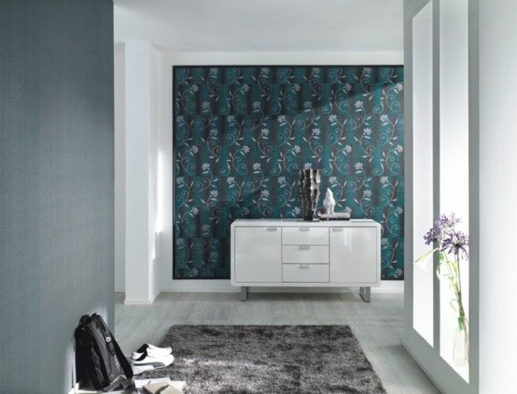 Textilní tapeta s okrasným vzorem a komoda s dekoracemi