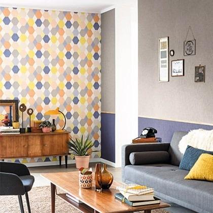 Barevná tapeta na zeď a pohovka s polštářky v obývacím pokoji