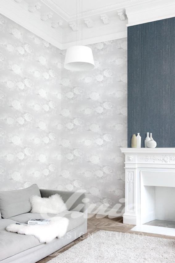 Vzorovaná tapeta na zeď, pohovka s polštářkem, krb s dekoracemi