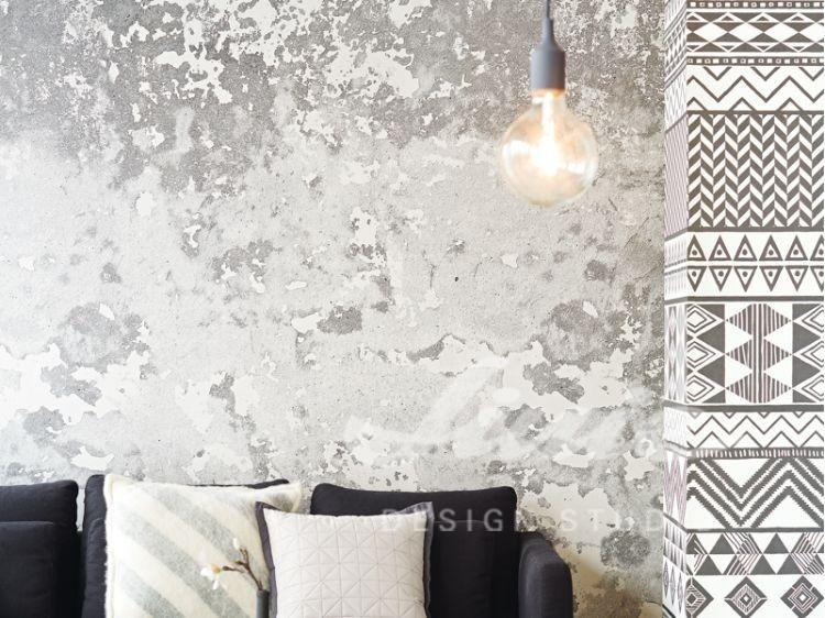 Pohovka s polštářky, stropní svítidlo, vzorovaná tapeta na zeď