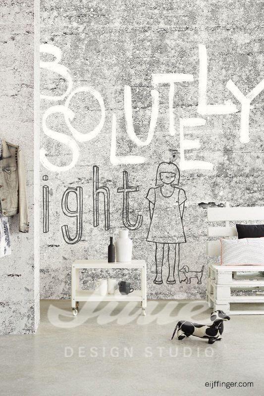 Stolek se dvěma vázami, lavice s polštářky, nástěnná tapeta s nápisy