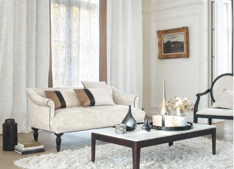 Pohovka s polštářky a konferenční stolek s dekoracemi