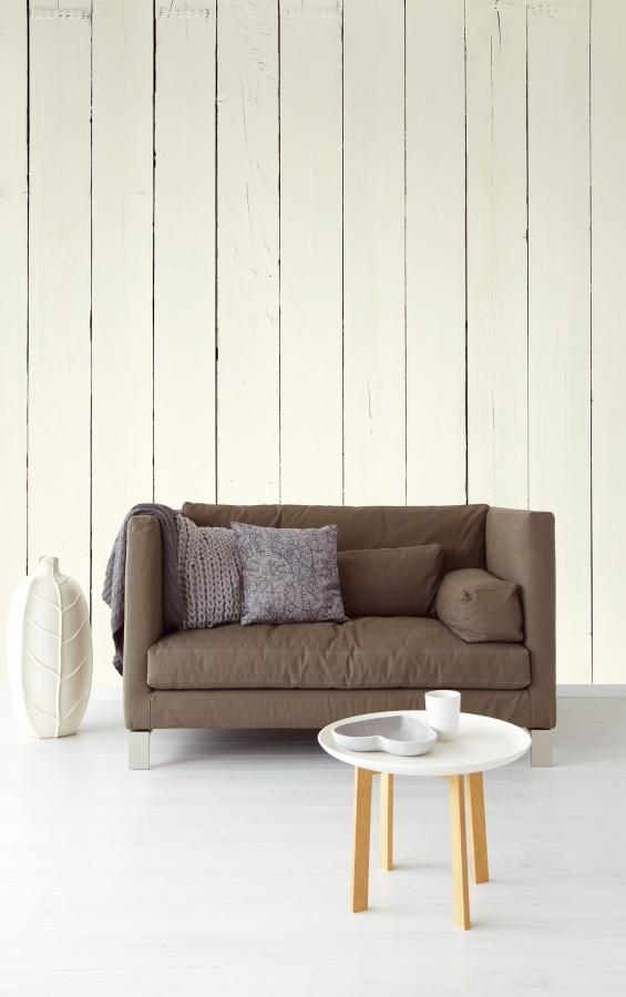 Tmavá pohovka, bílý stolek a bílá tapeta dřeva