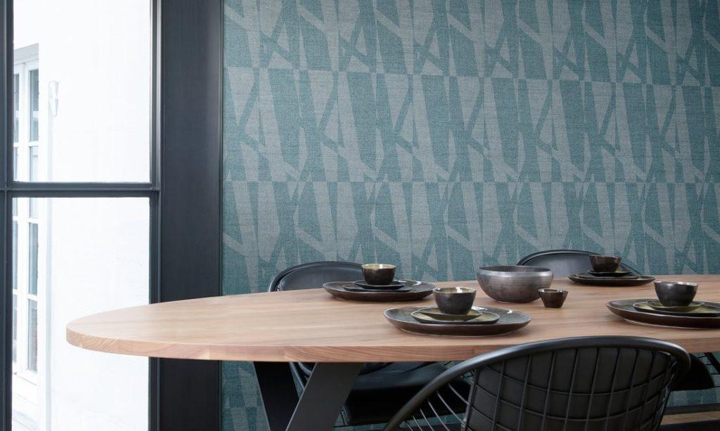 Nástěnná tapeta s abstraktním vzorem a jídelní stůl s nádobím