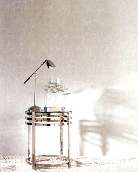 Stříbrný stolek s lampou a skleněnou vázou ve světlé místnosti