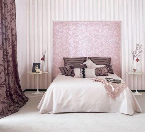 Manželská postel s polštářky ve světlé místnosti