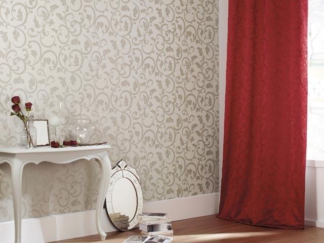 Bílý stolek s květinami, stříbrné zrcadlo opřené o bílou stěnu s ornamenty a závěs