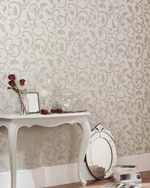 Bílý stolek s květinami a stříbrné zrcadlo opřené o bílou stěnu s šedými ornamenty