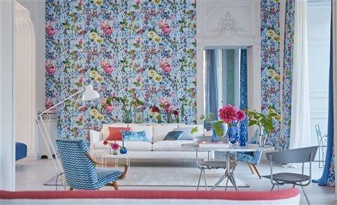 Květinová tapeta na zeď a pohovka s polštářky