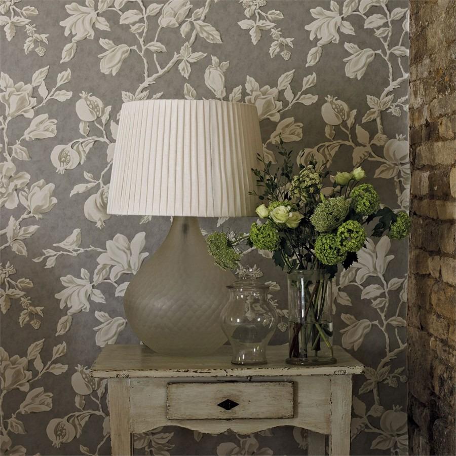 Nástěnná tapeta s přírodním motivem a stolek s lampou a dekoracemi