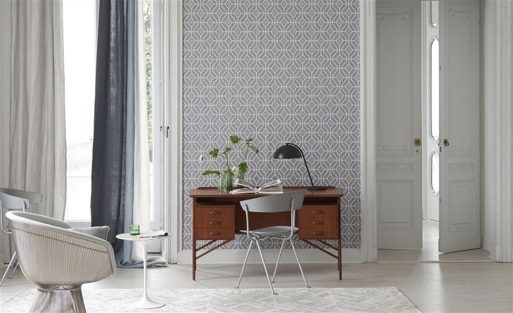 Nástěnná tapeta s pravidelným vzorem a psací stůl s lampou a dekoracemi