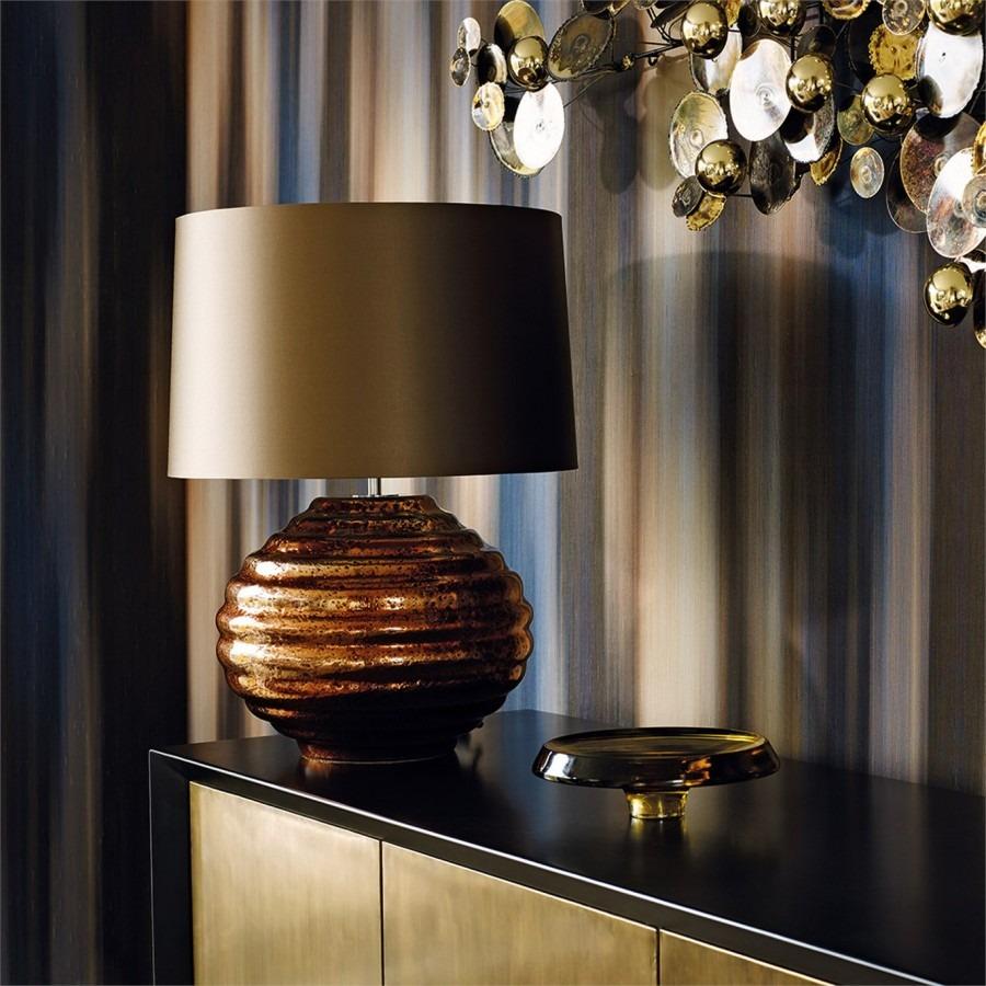Nástěnná tapeta s abstraktním vzorem a stůl s lampou a dekorací