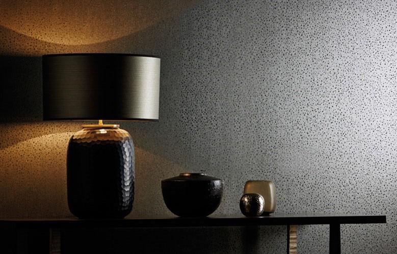 Nástěná tapeta s tečkami a stůl s lampou a dekoracemi