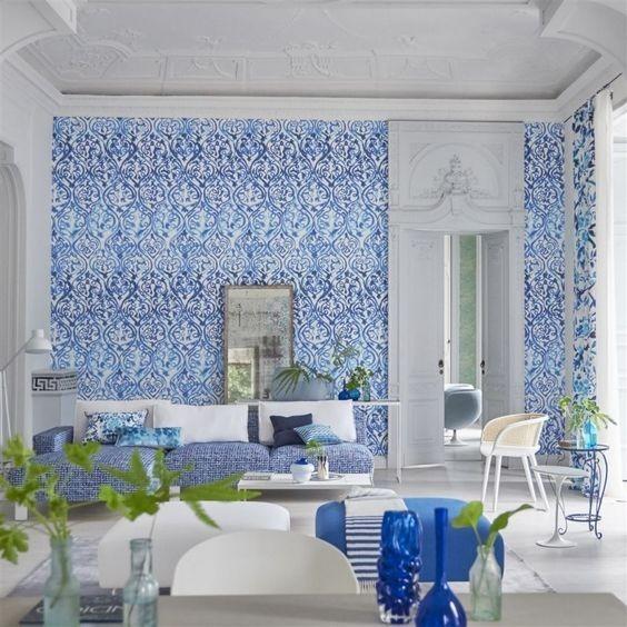 Vzorovaná tapeta na zeď a pohovka s polštářky v obývacím pokoji