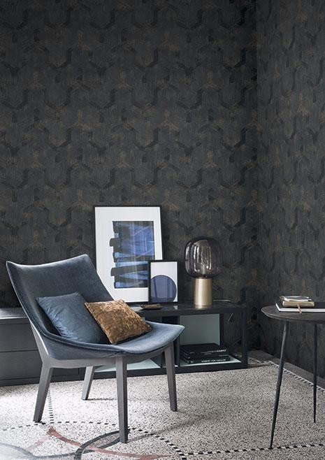 Tmavá nástěnná tapeta a křeslo s polštářky v obývacím pokoji