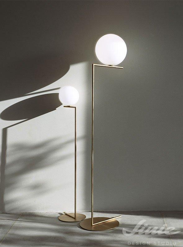 zlatá stojací kovová lampa flos se skleněnou koulí